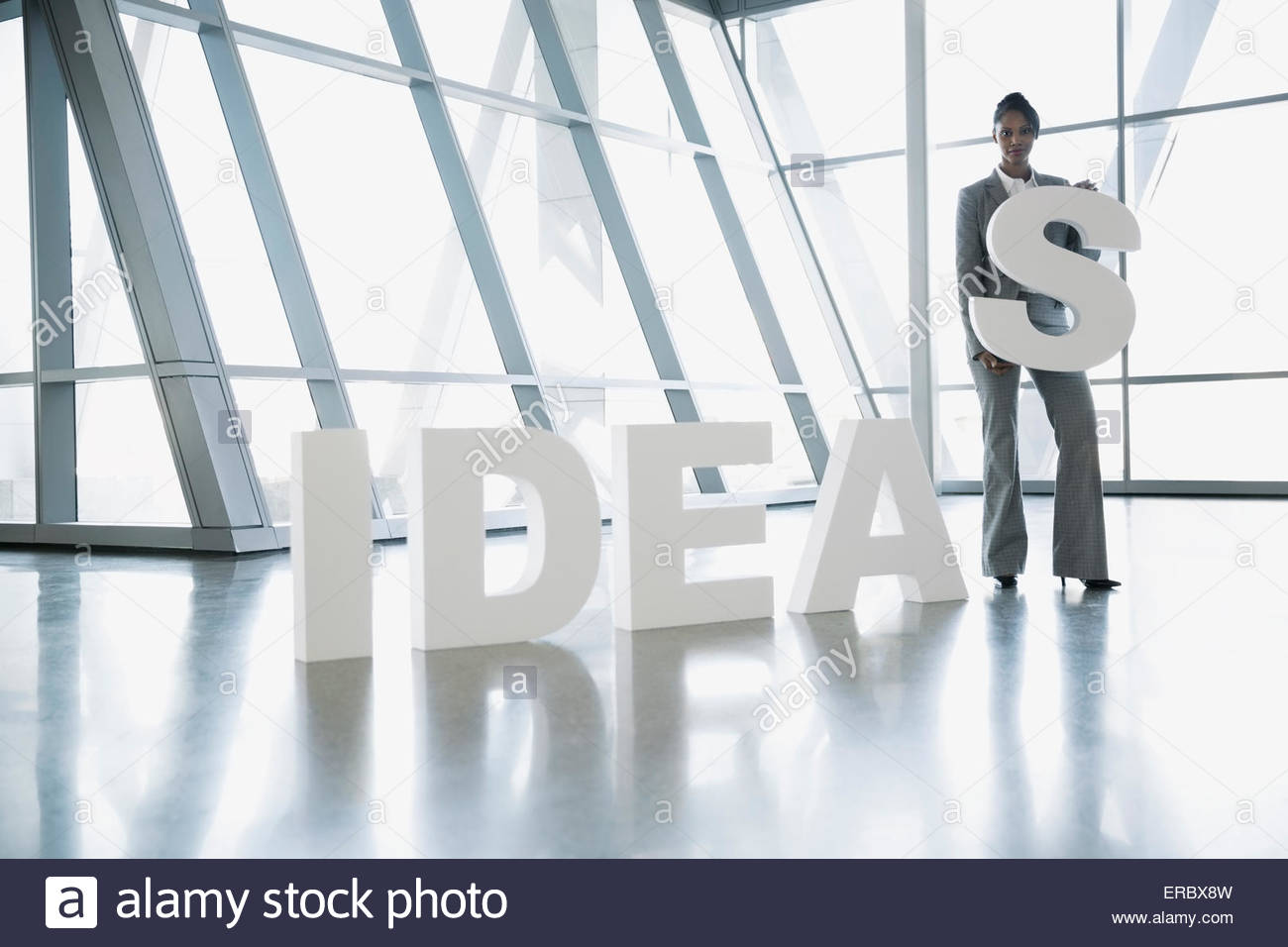 Portrait businesswoman holding letter S in 'Ideas' - Stock Image