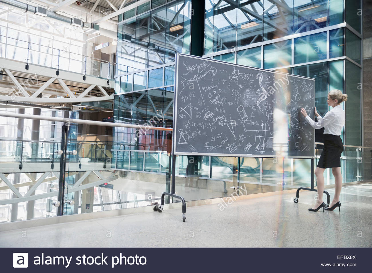 Businesswoman writing complex equations on blackboard in atrium - Stock Image