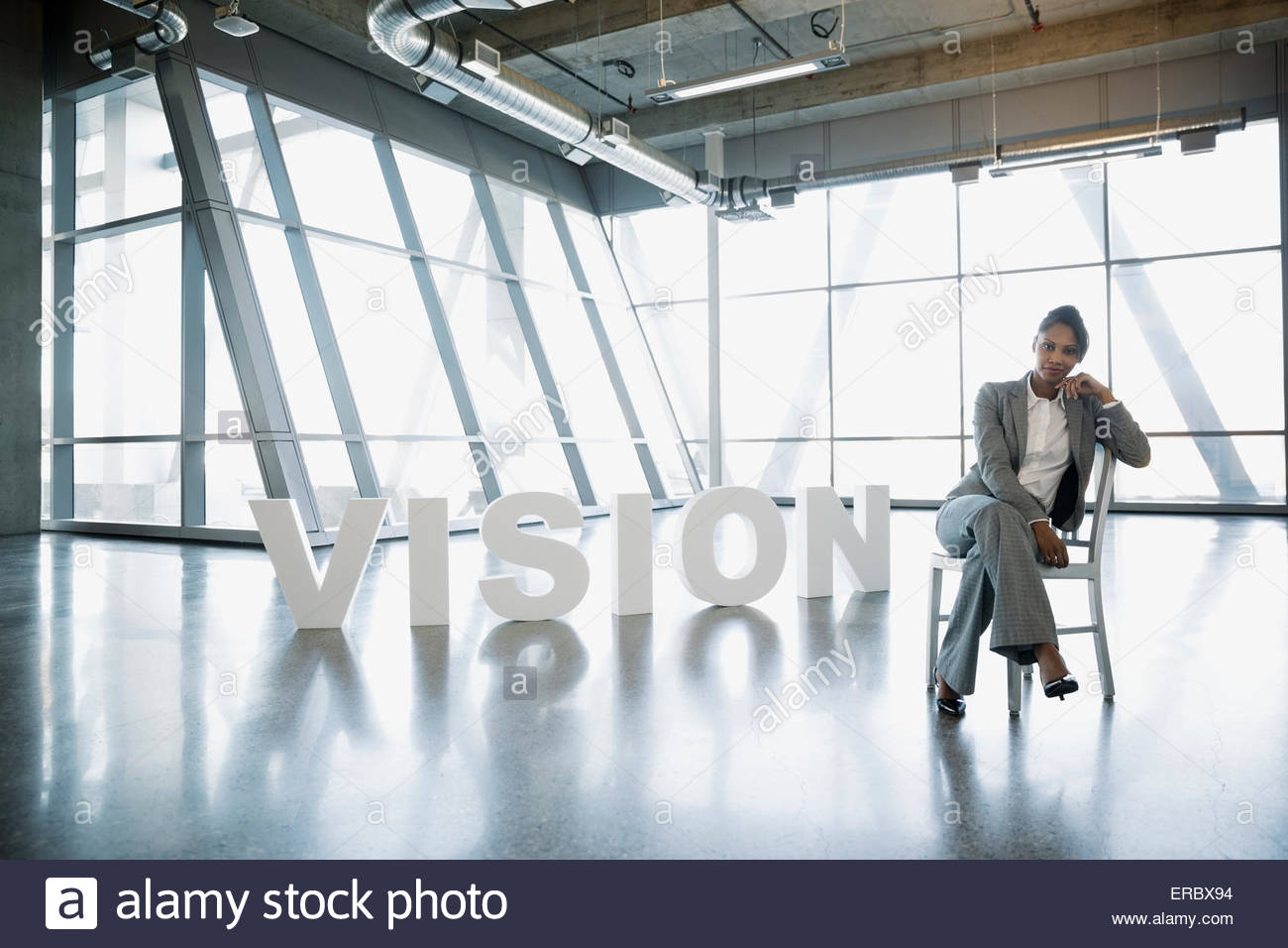 Portrait businesswoman sitting next to 'Vision' letters - Stock Image