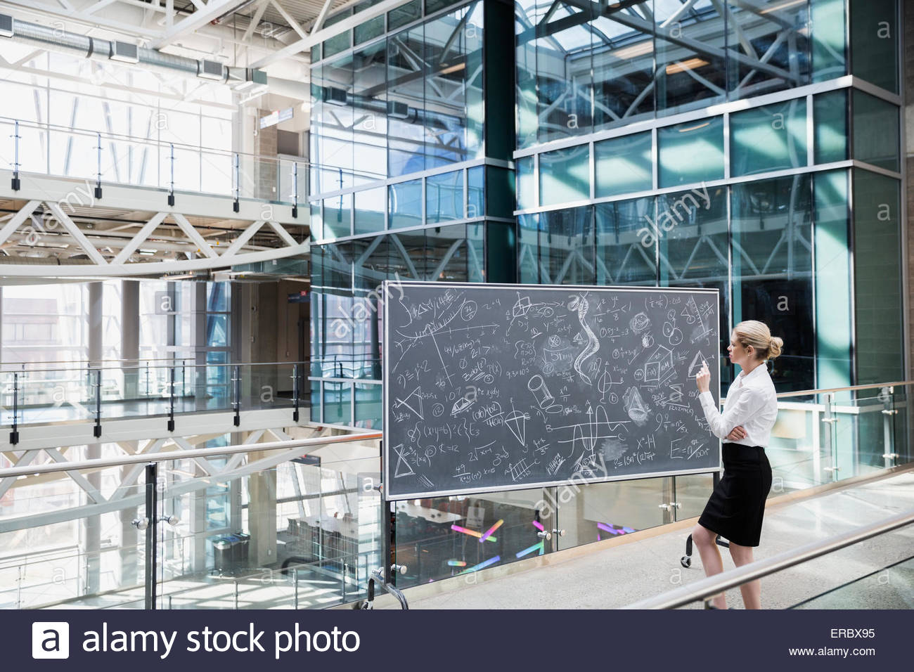 Businesswoman at blackboard with complex equations in atrium - Stock Image