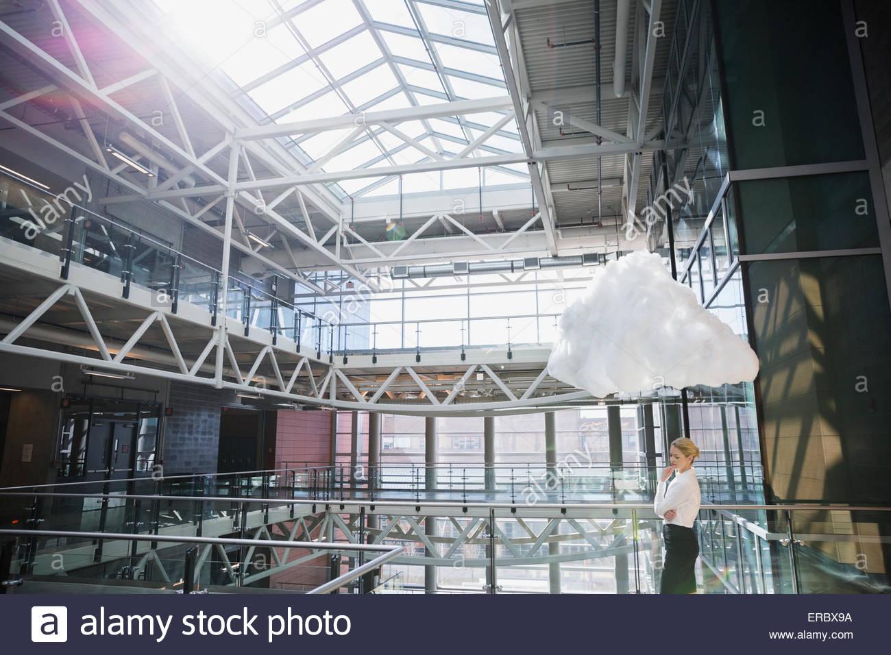 Cloud over pensive businesswoman in sunny atrium - Stock Image
