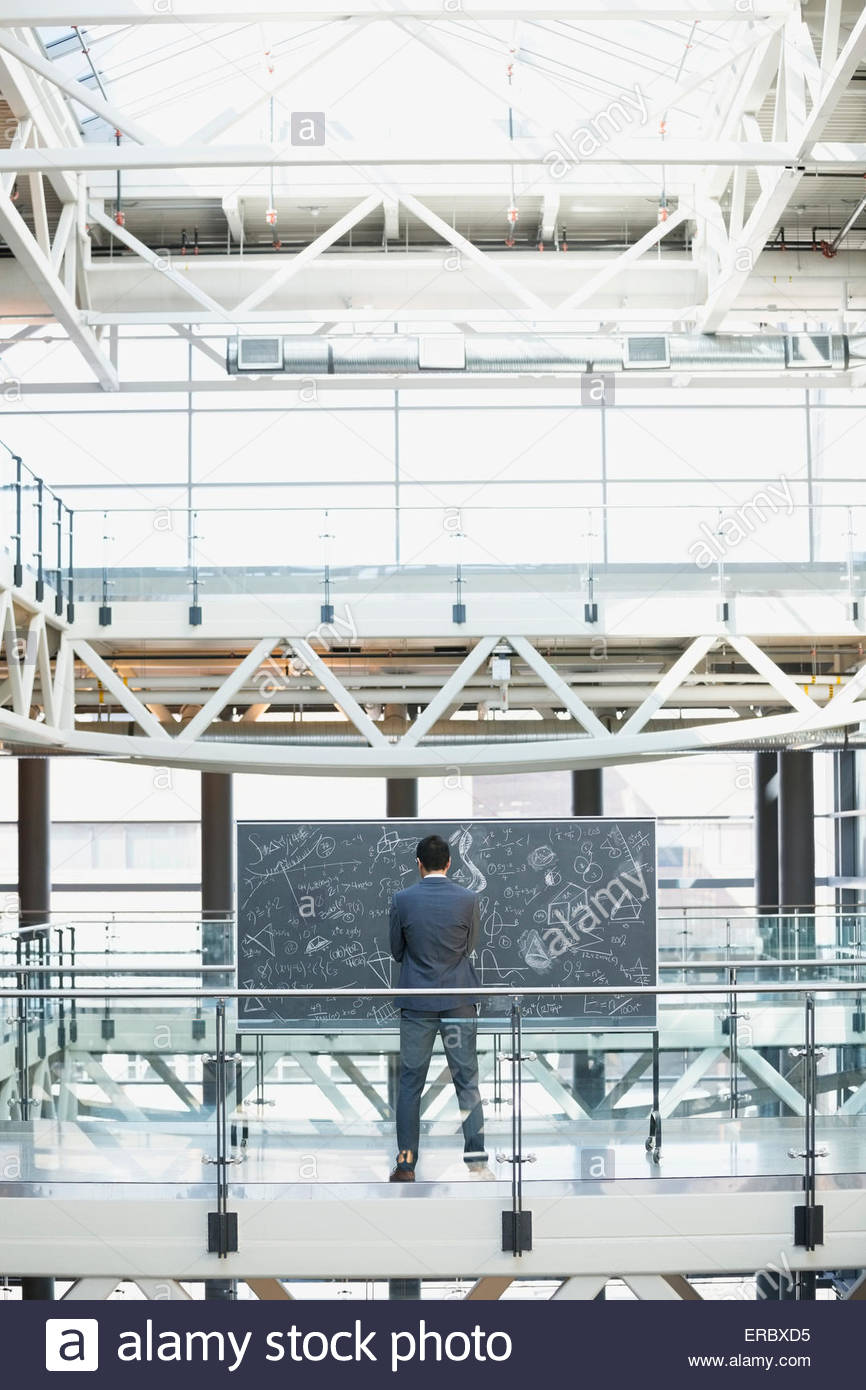 Businessman at blackboard with complex equations in atrium - Stock Image
