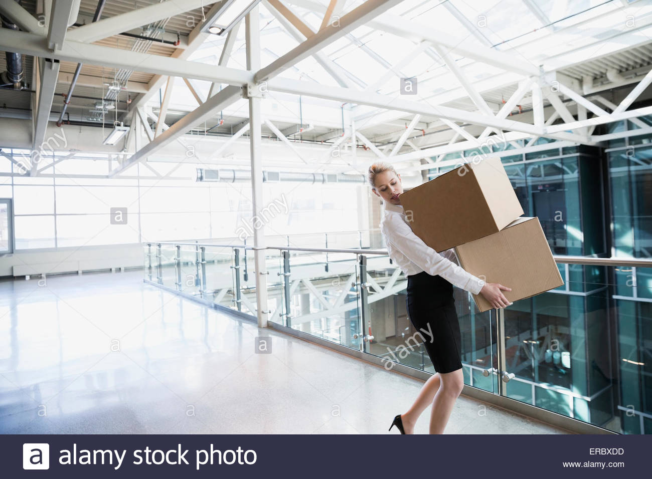 Businesswoman carrying cardboard boxes in atrium - Stock Image