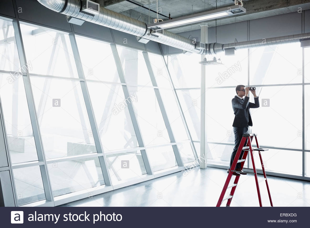 Businessman on ladder with binoculars in modern office - Stock Image