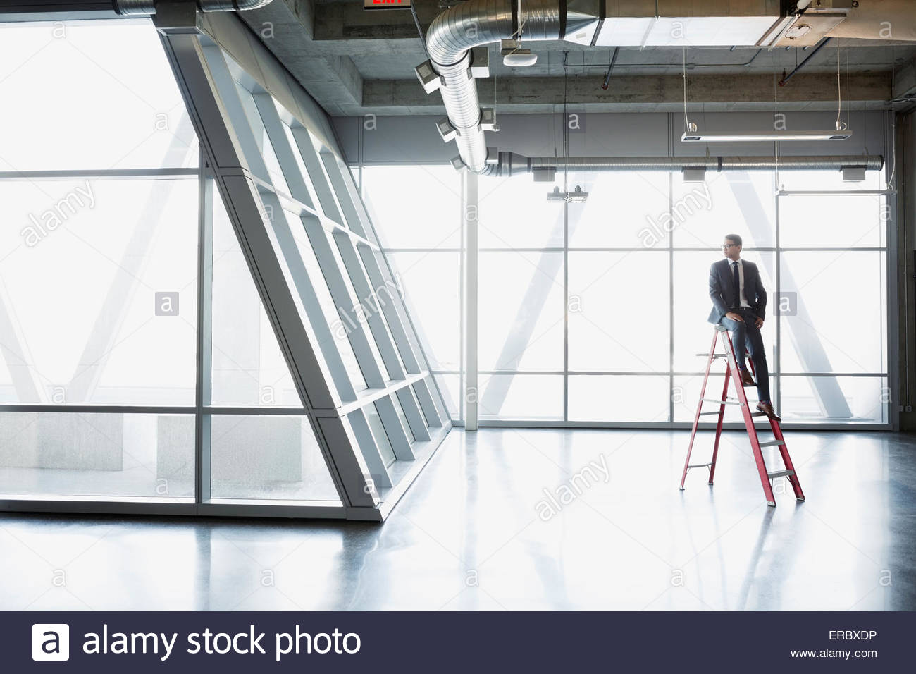 Businessman sitting on ladder in empty modern office - Stock Image