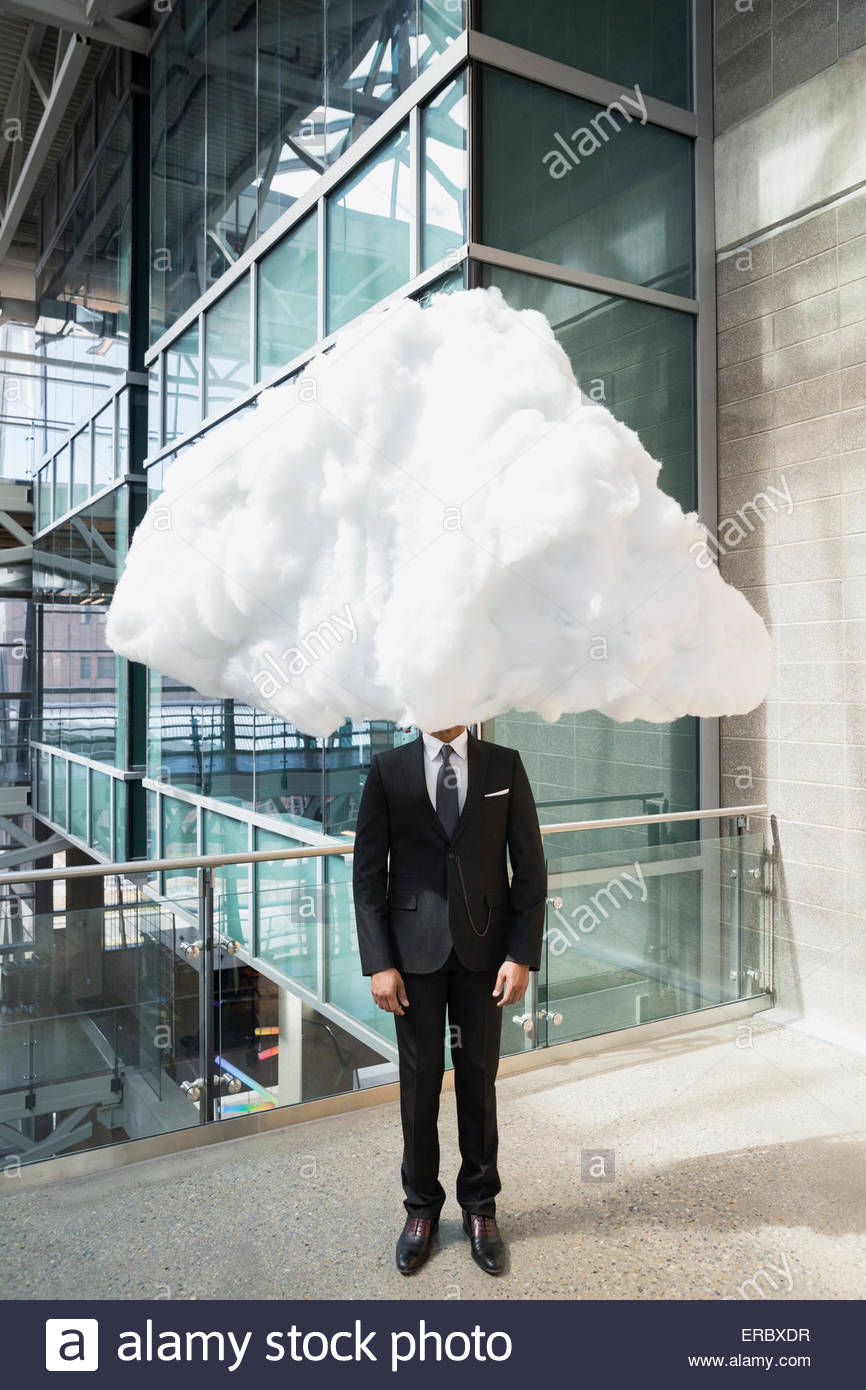 Businessman with head in clouds on atrium balcony - Stock Image