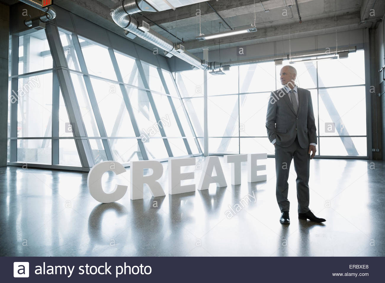 Businessman near 'Create' letters looking away - Stock Image