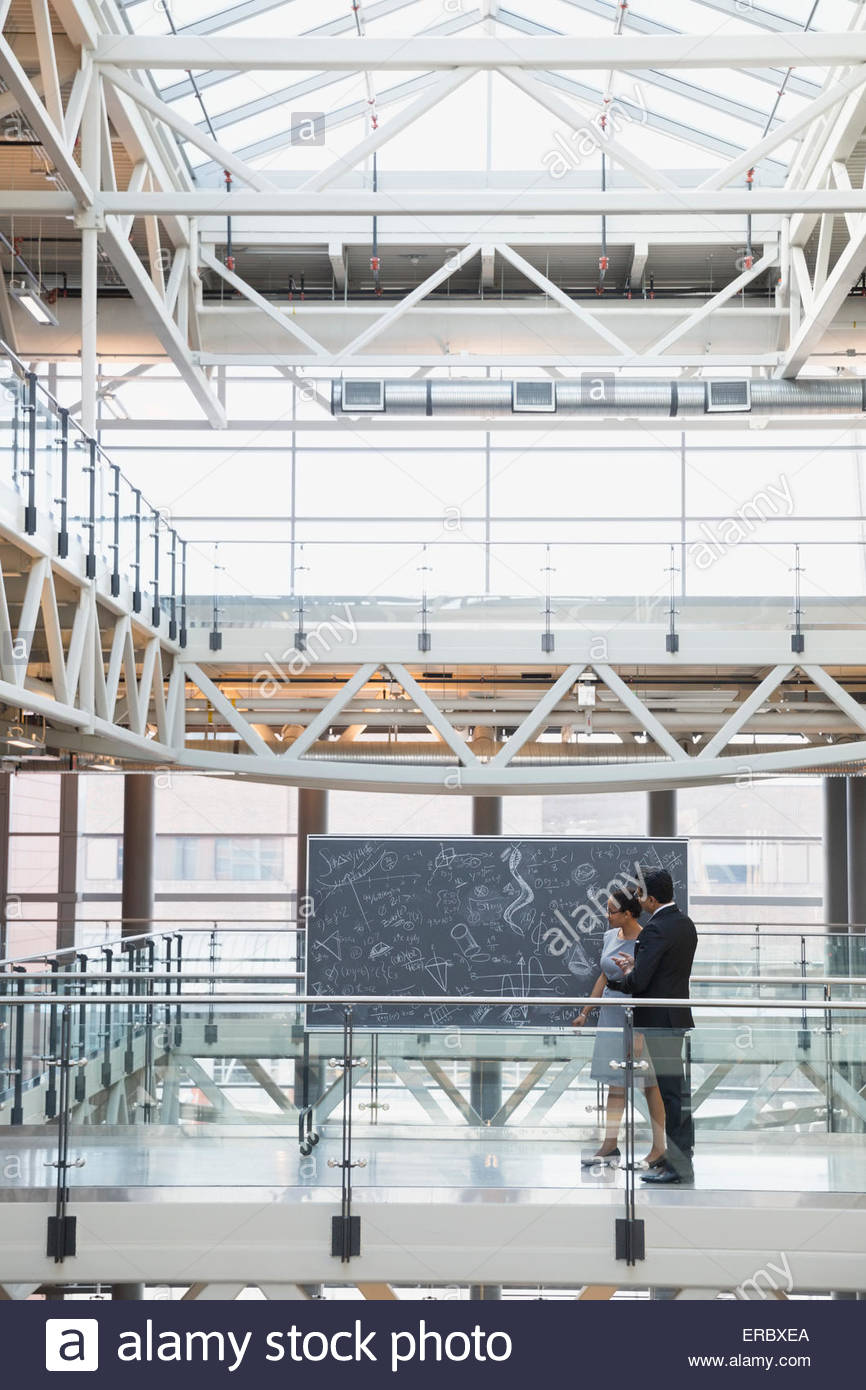 Business people at blackboard with complex equations atrium - Stock Image