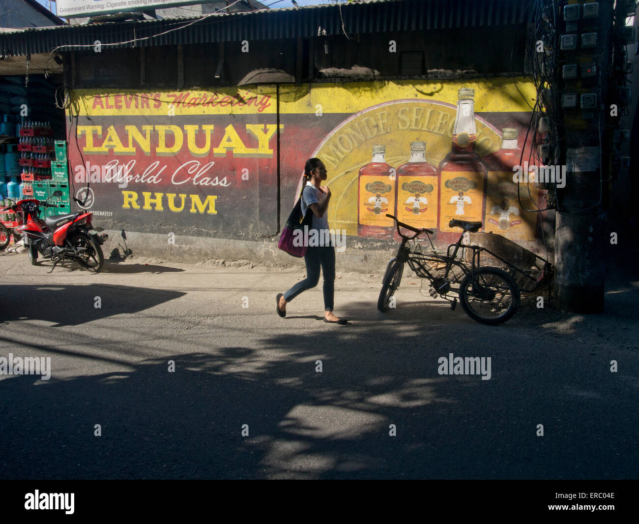 Woman walking on the street by a advertisement for rhum in Ilo Ilo, Philippines - Stock Image