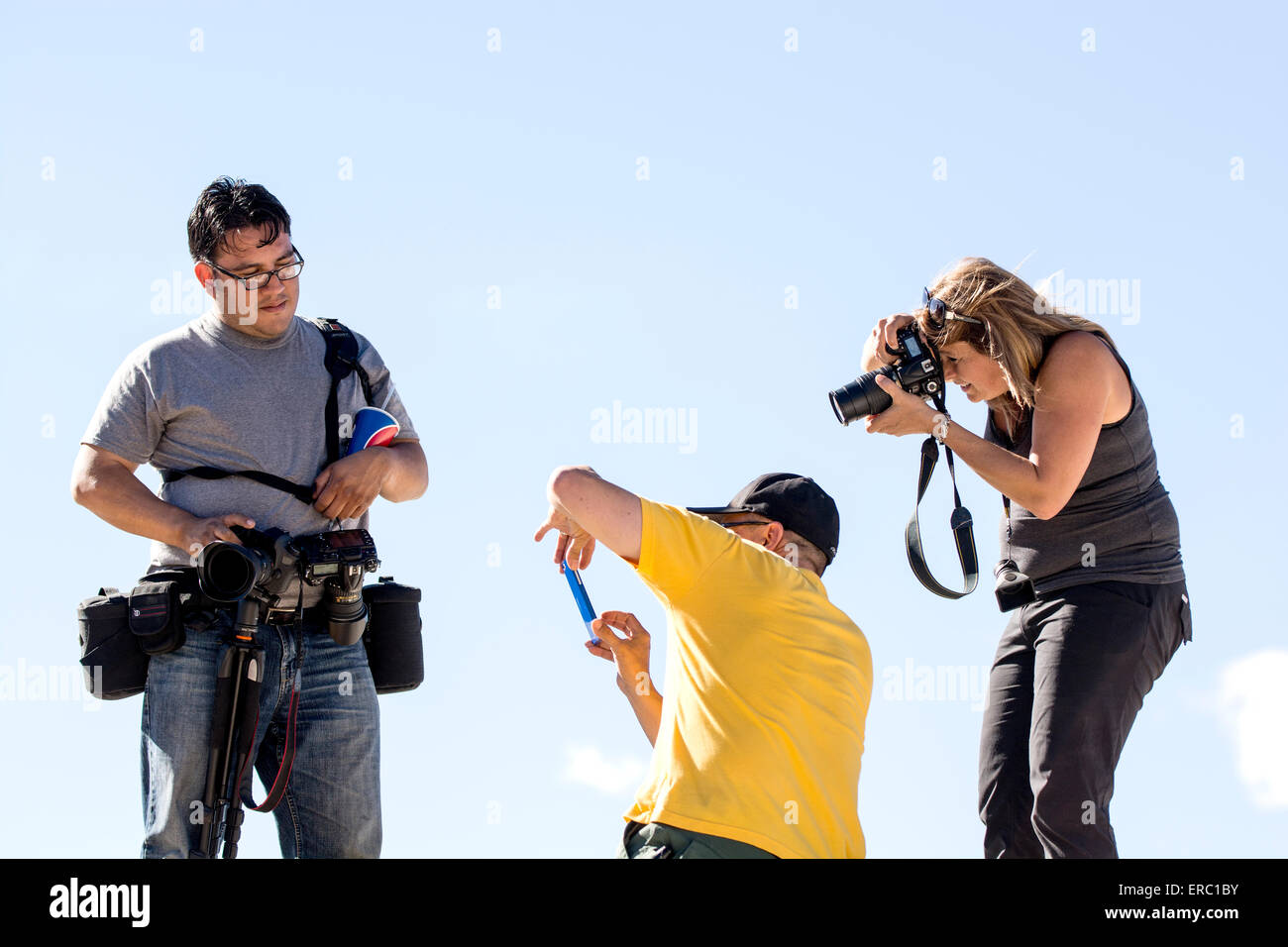 Three photographers together with one modeling. - Stock Image