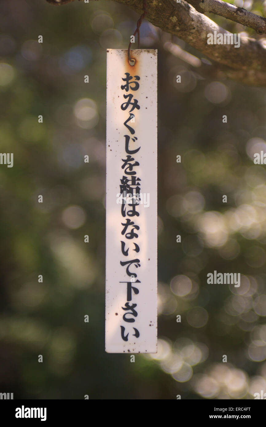 A sign asking visitors not to tie their unwanted fortune papers on to a tree in the gardens of Narita Jinja (Shrine), - Stock Image