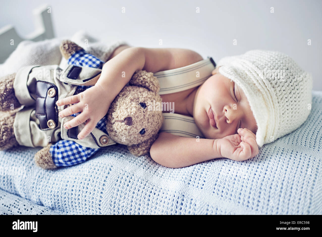 Newborn child sleeping with a teddy bear toy - Stock Image