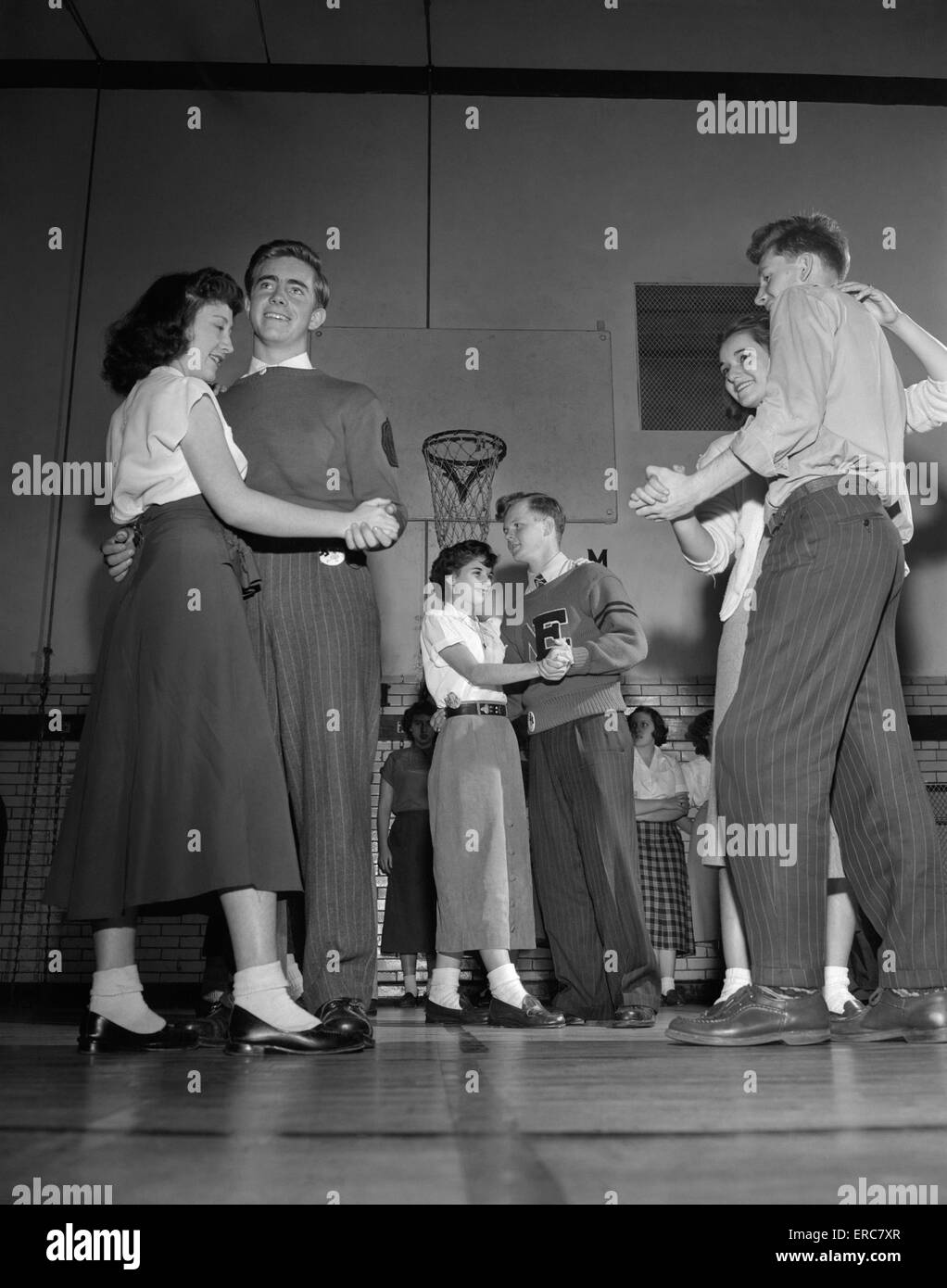 4a49f7e43c04 1940s 1950s TEENAGE BOYS AND GIRLS DANCING SLOW DANCE AT PARTY IN HIGH  SCHOOL GYMNASIUM -