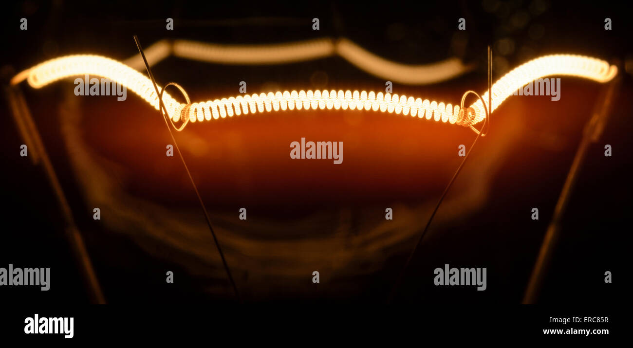 Filament of an incandescent electric light bulb, turned on. - Stock Image