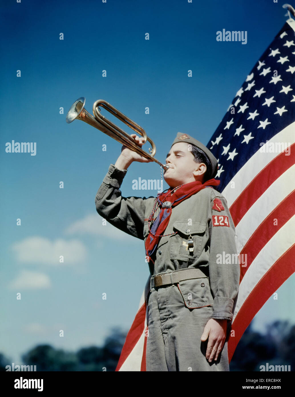 1950s BOY SCOUT BLOWING BUGLE IN FRONT OF 48 STAR AMERICAN FLAG - Stock Image