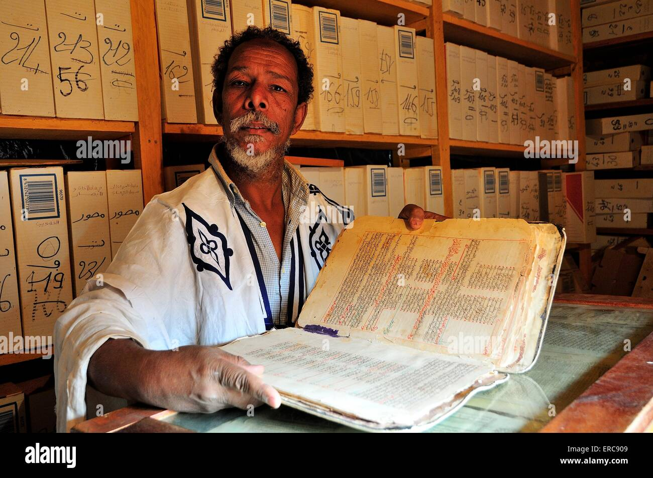 Scholar, old man with a valuable book an Islamic library in the historic centre, Chinguetti, Adrar Region, Mauritania Stock Photo