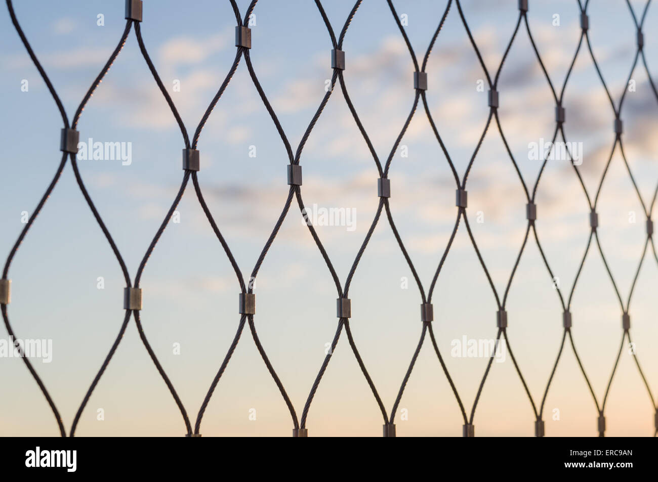 Metal mesh wire fence closeup sunset sky background Stock Photo ...