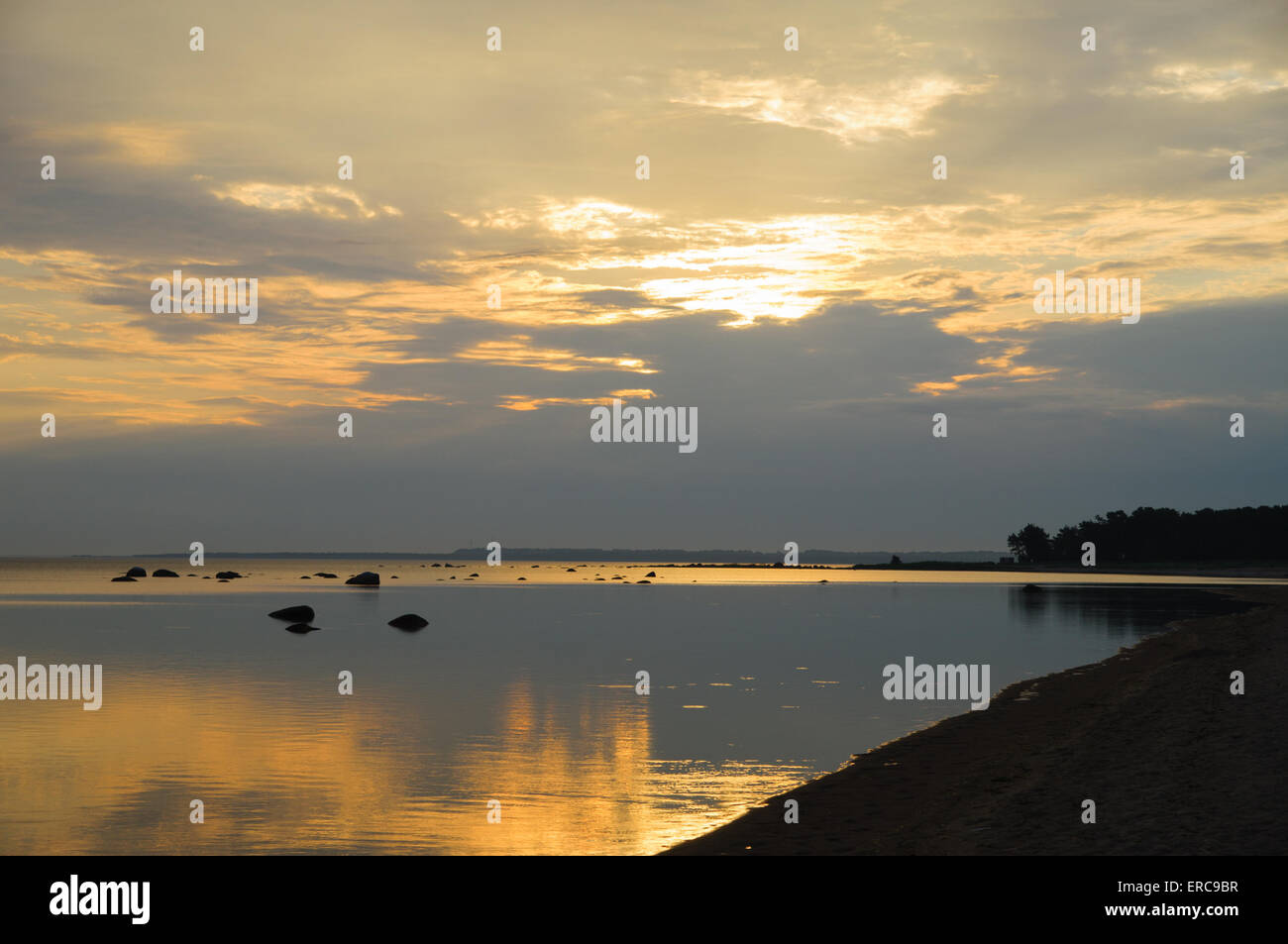 Sunrise over coastline silhouette - Stock Image