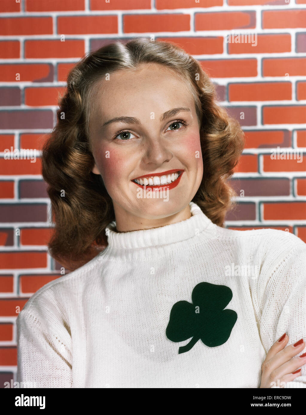 1940s 1950s PORTRAIT SMILING WOMAN WEARING WHITE SWEATER WITH SHAMROCK DESIGN LOOKING AT CAMERA - Stock Image