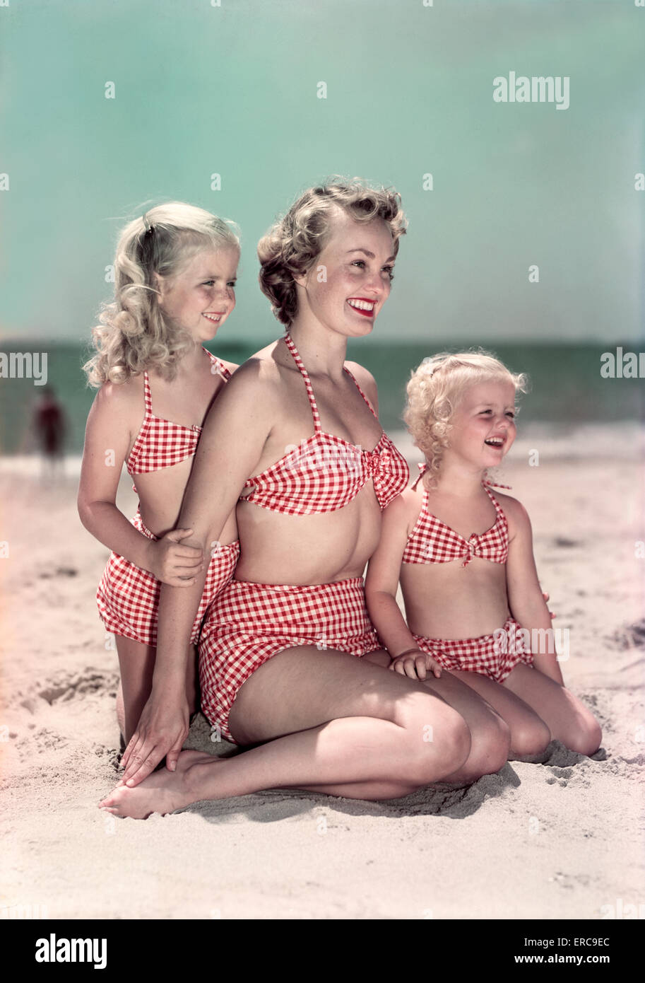 1950s PORTRAIT SMILING MOTHER AND TWO DAUGHTERS WEARING MATCHING CHECKED TWO PIECE BATHING SUITS SITTING POSING - Stock Image