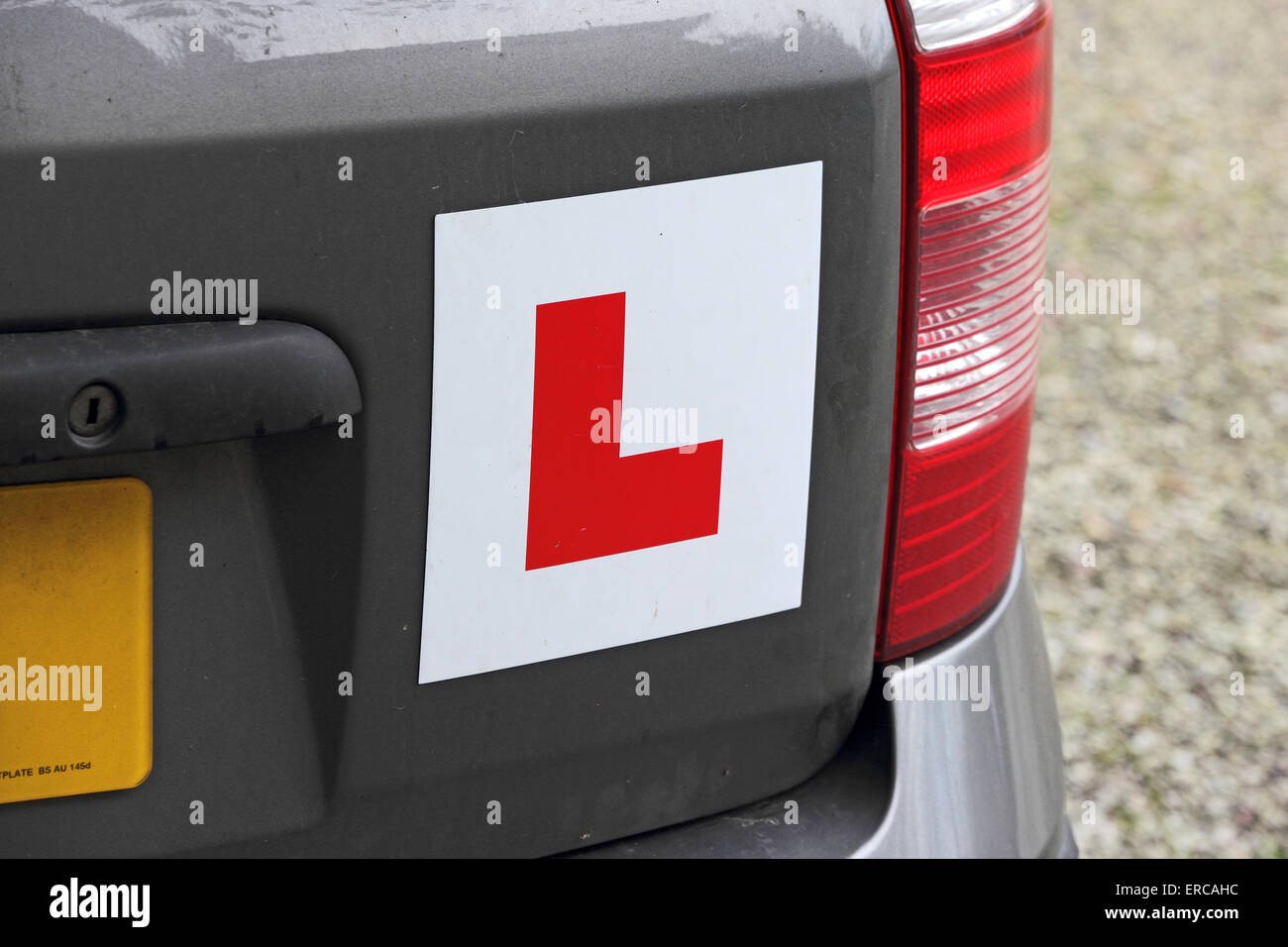 L plate attached to rear of small dark coloured car Stock Photo