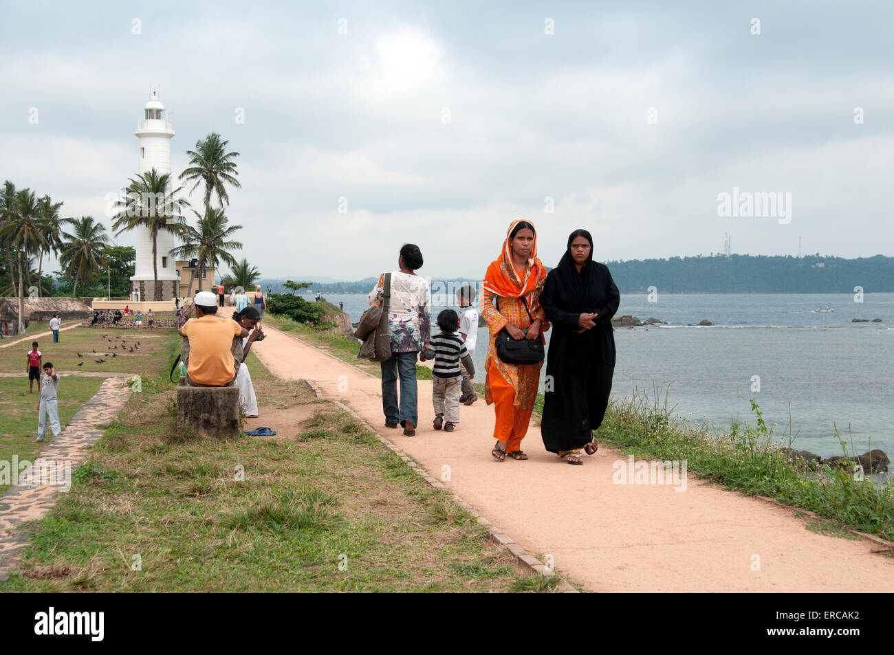 Galle Fort lighthouse early evening with Muslim families on the sea wall path Galle Fort Sri Lanka - Stock Image