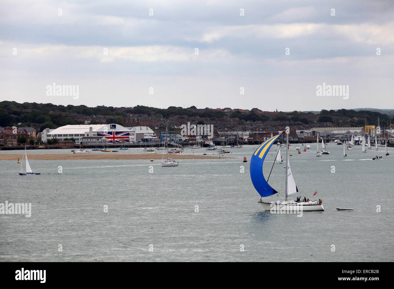 Yachts sail past Venture Quays in Cowes on the Isle of Wight which has the world's largest Union Flag painted - Stock Image