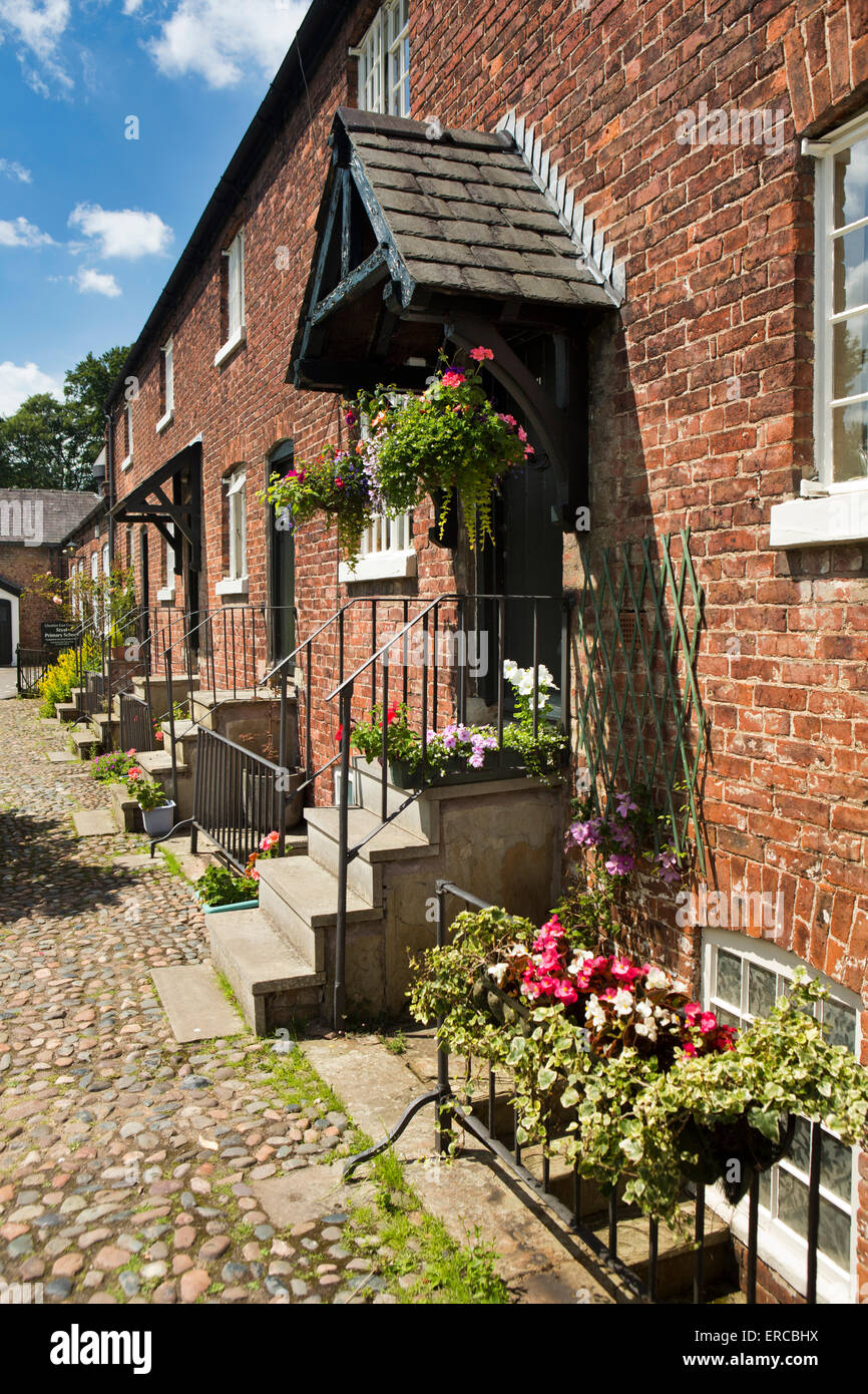 UK, England, Cheshire, Styal, Oak Cottages and gardens, terrace of mill workers houses leading to village school - Stock Image