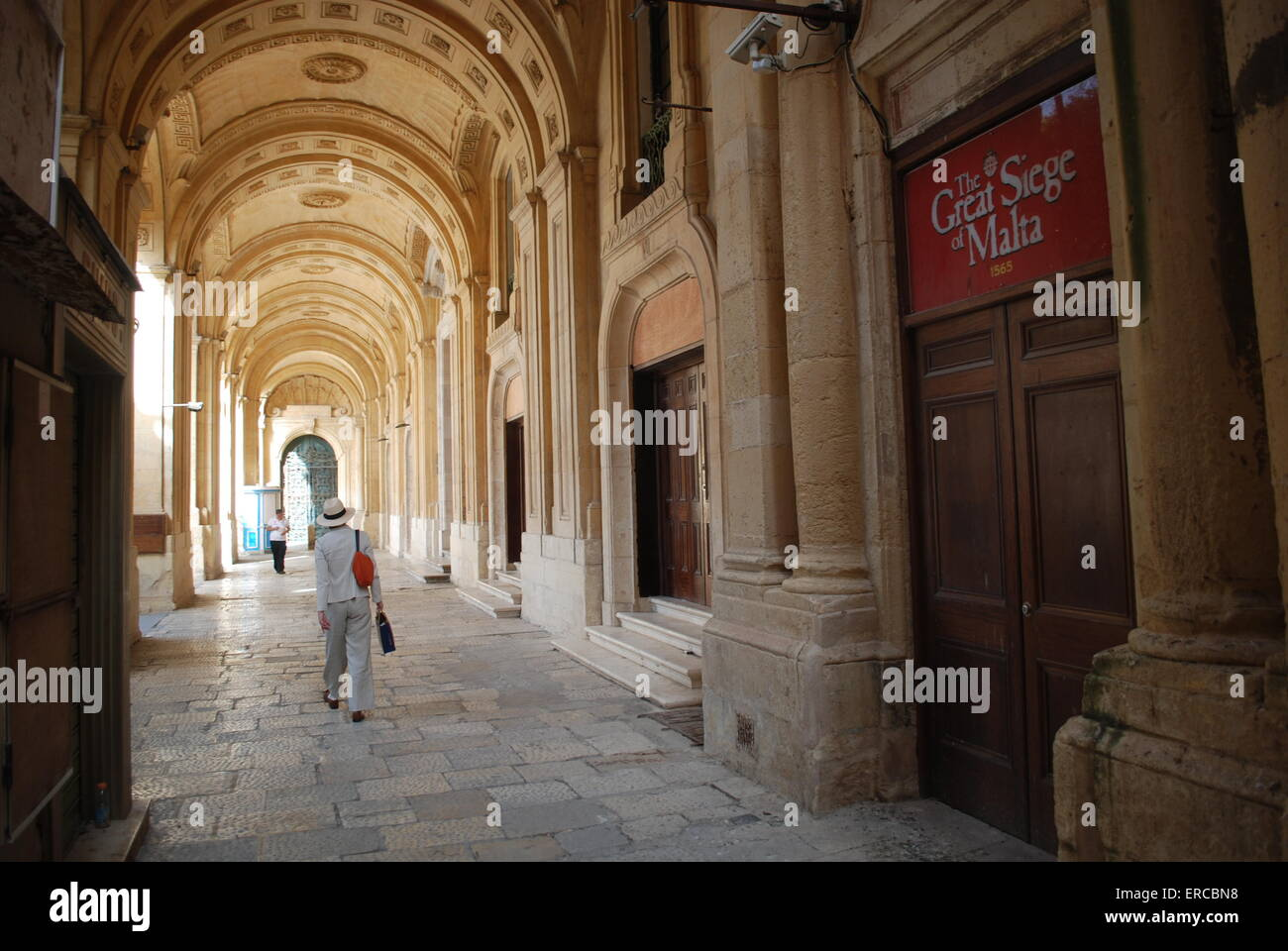 A tourist in Valletta walks past a sign commemorating the 450th anniversary of the Great Siege of Malta. Pix by: - Stock Image