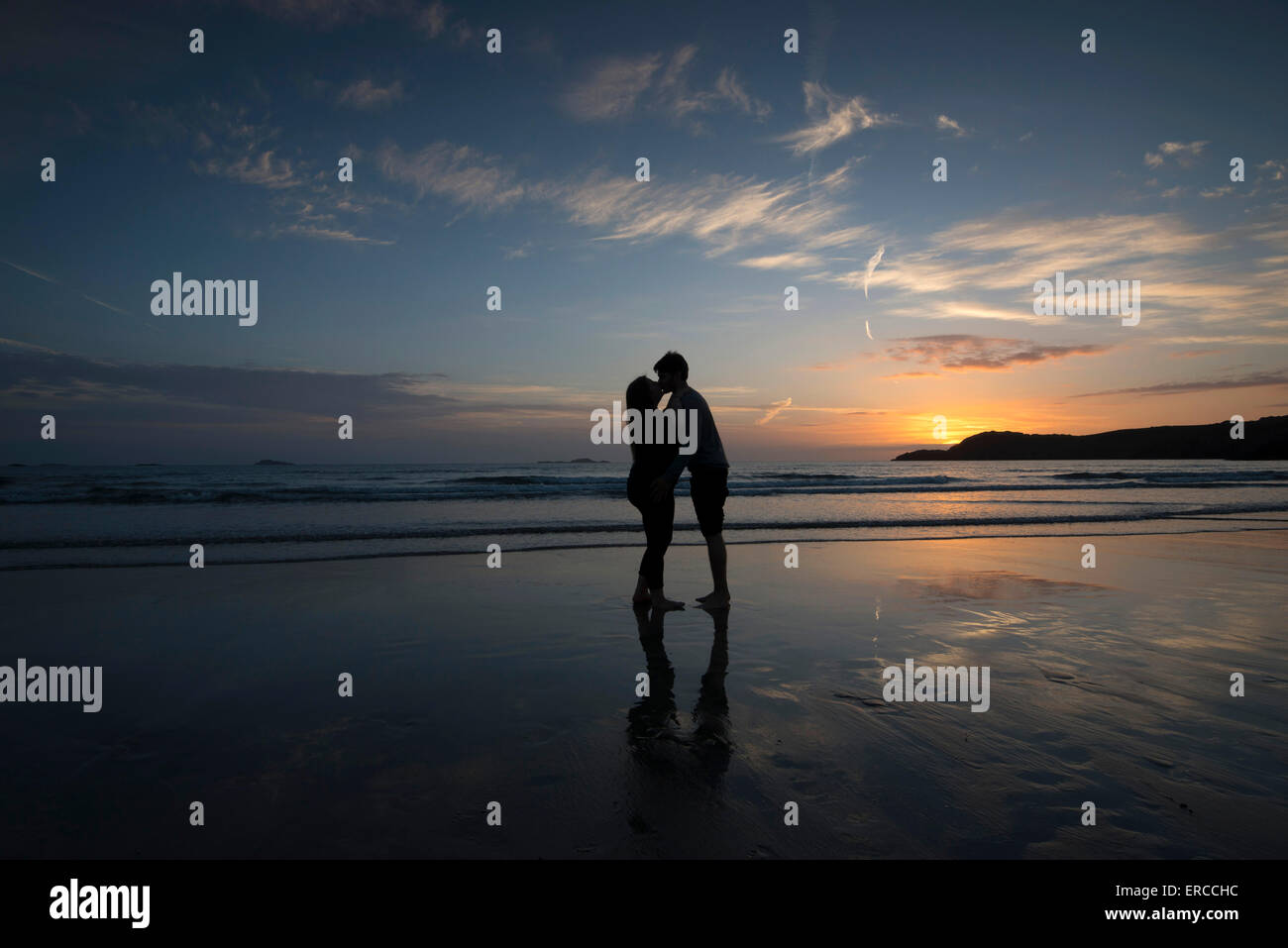A young couple silhouetted on the beach at sunset on Whitesands Beach in St Davids, Pembrokeshire Wales - Stock Image