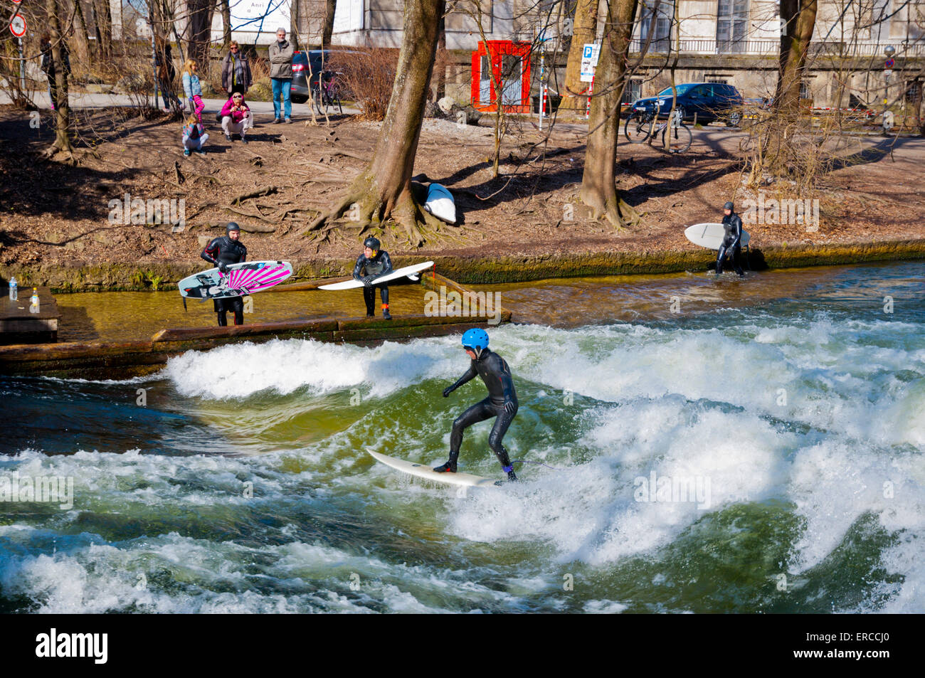 Surfers at wave produced by pumping machine, Eisbach stream, Englischer Garten, park, central Munich, Bavaria, Germany - Stock Image
