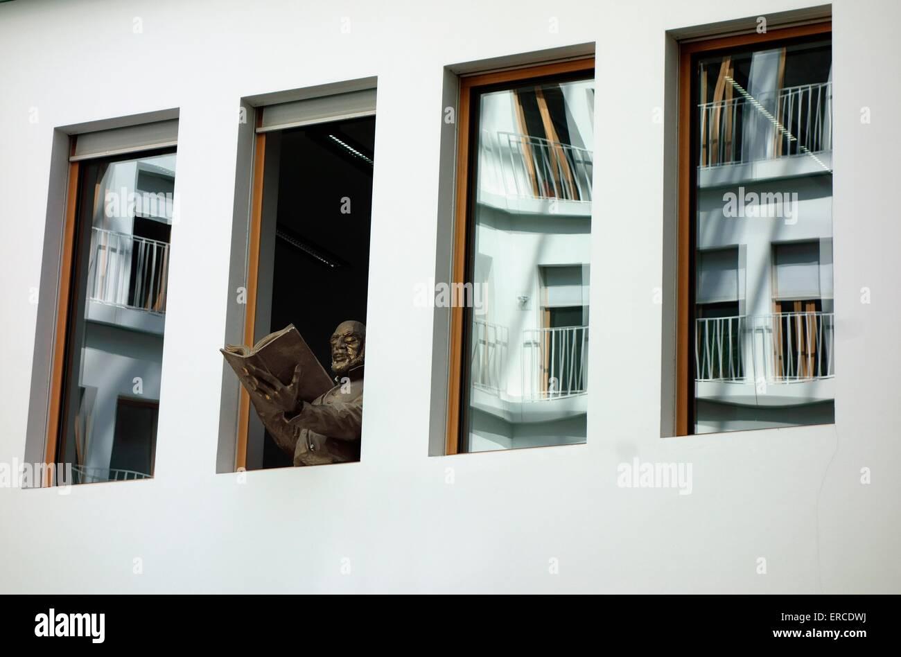 Sculpture reading book through windows in Foyer of modern office building Berlin - Stock Image
