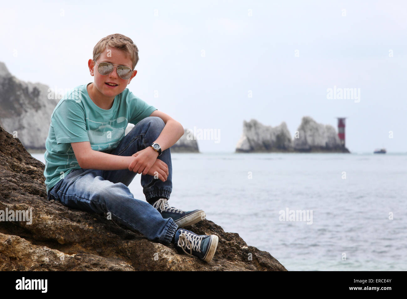 A boy on a rock enjoying the view at The Needles on the Isle of Wight - Stock Image
