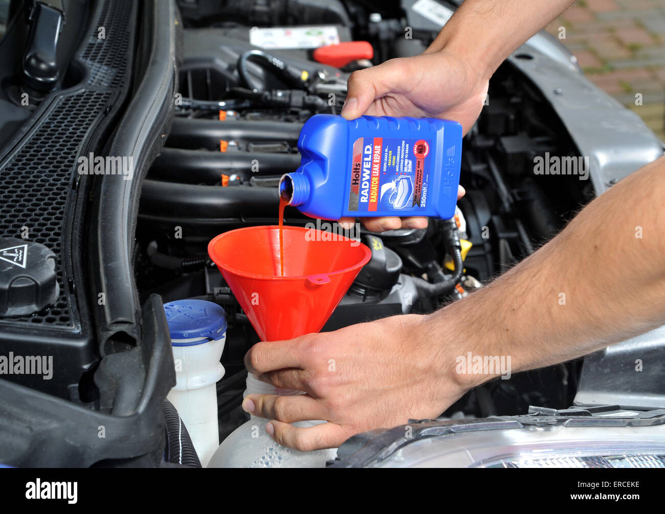 Pouring Radiator Repair Liquid Into A Car Cooling System
