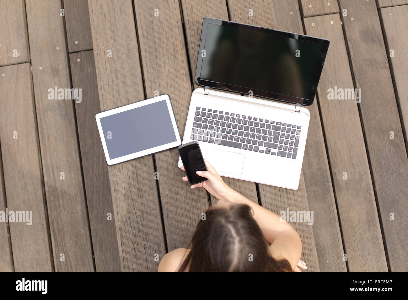 Woman using multiple devices phone laptop and tablet lying in a wood bench in a park - Stock Image