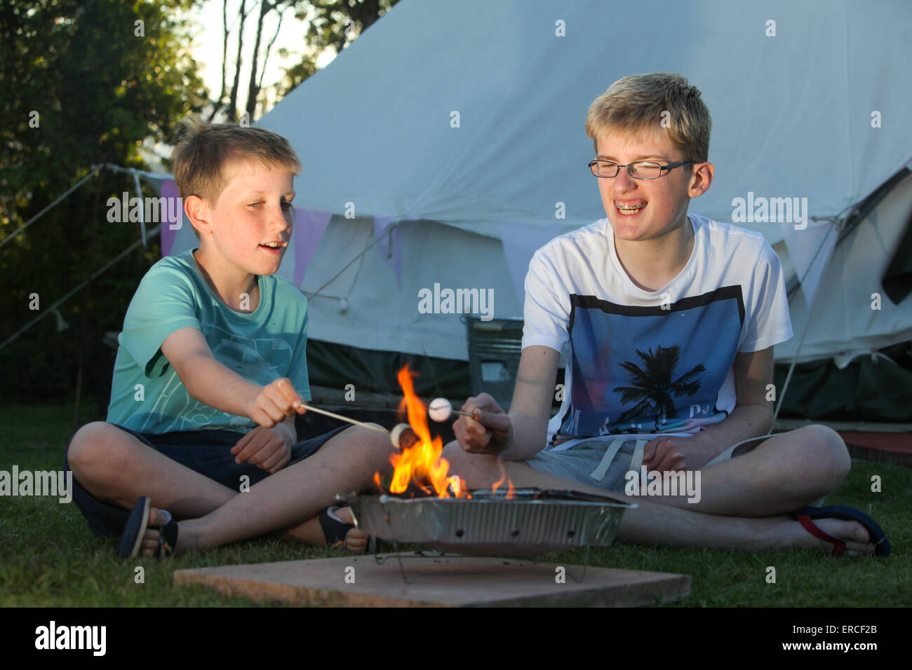 Children toasting marshmallows over a camp fire whilst glamping camping in the UK - Stock Image