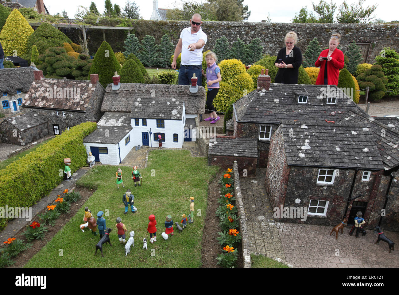 Tourists appear to be giants as they visit to The Model Village in Godshill on the Isle of Wight - Stock Image