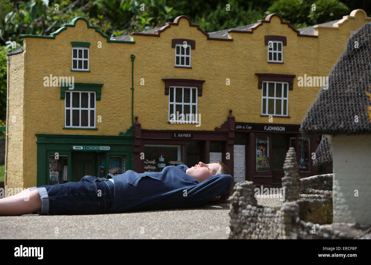 A boy relaxing in the sunshine during a visit to The Model Village in Godshill on the Isle of Wight - Stock Image