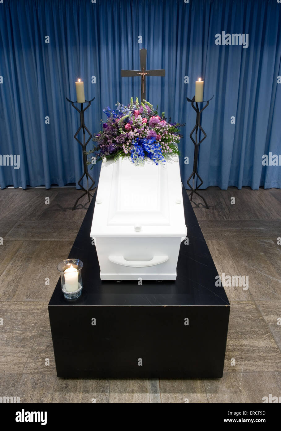 A coffin with a flower arrangement in a morgue with two burning candles and a cross - Stock Image