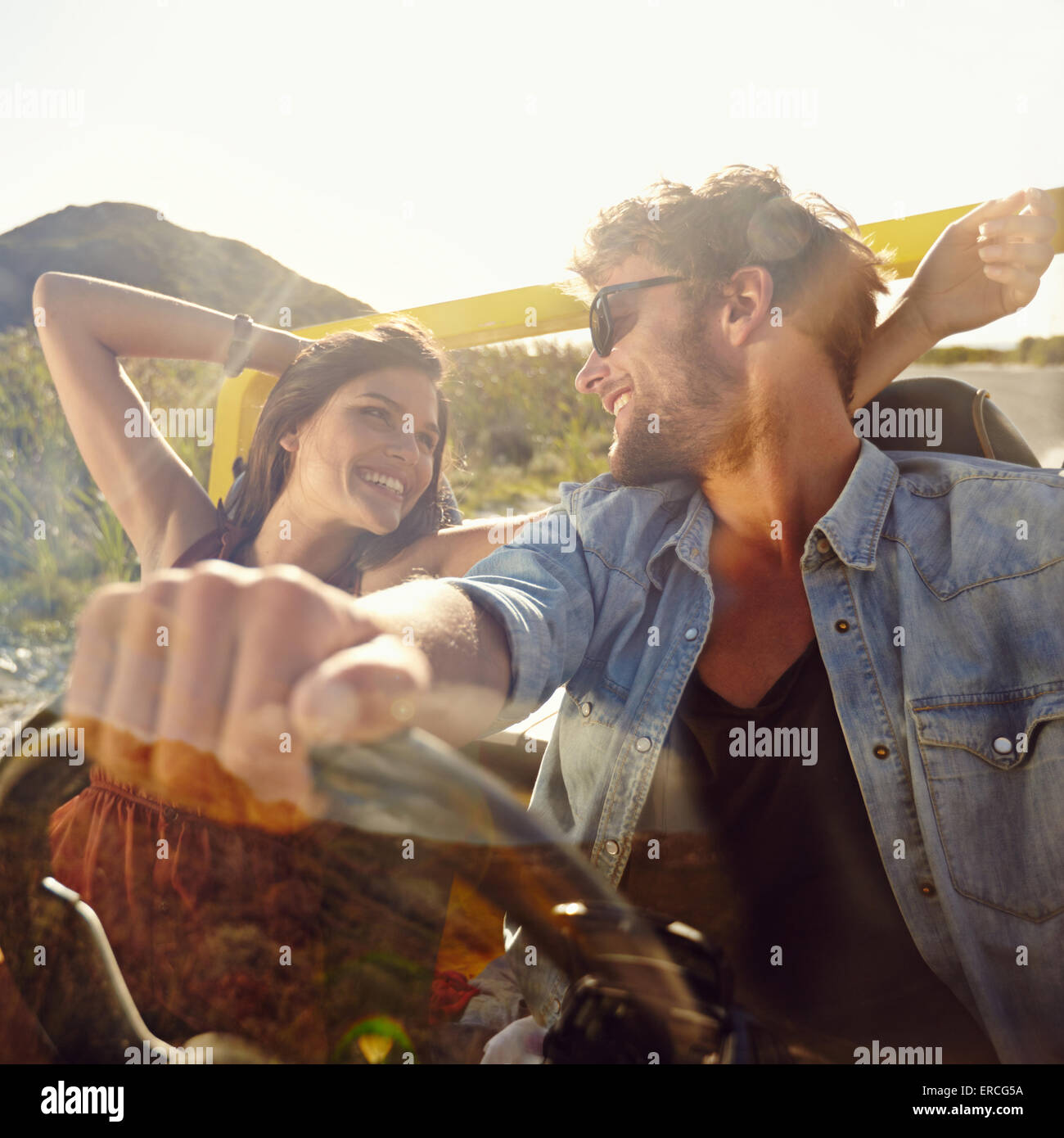Happy young man and woman in a car enjoying a road trip on a summer day. Couple out on a drive in a open car. - Stock Image