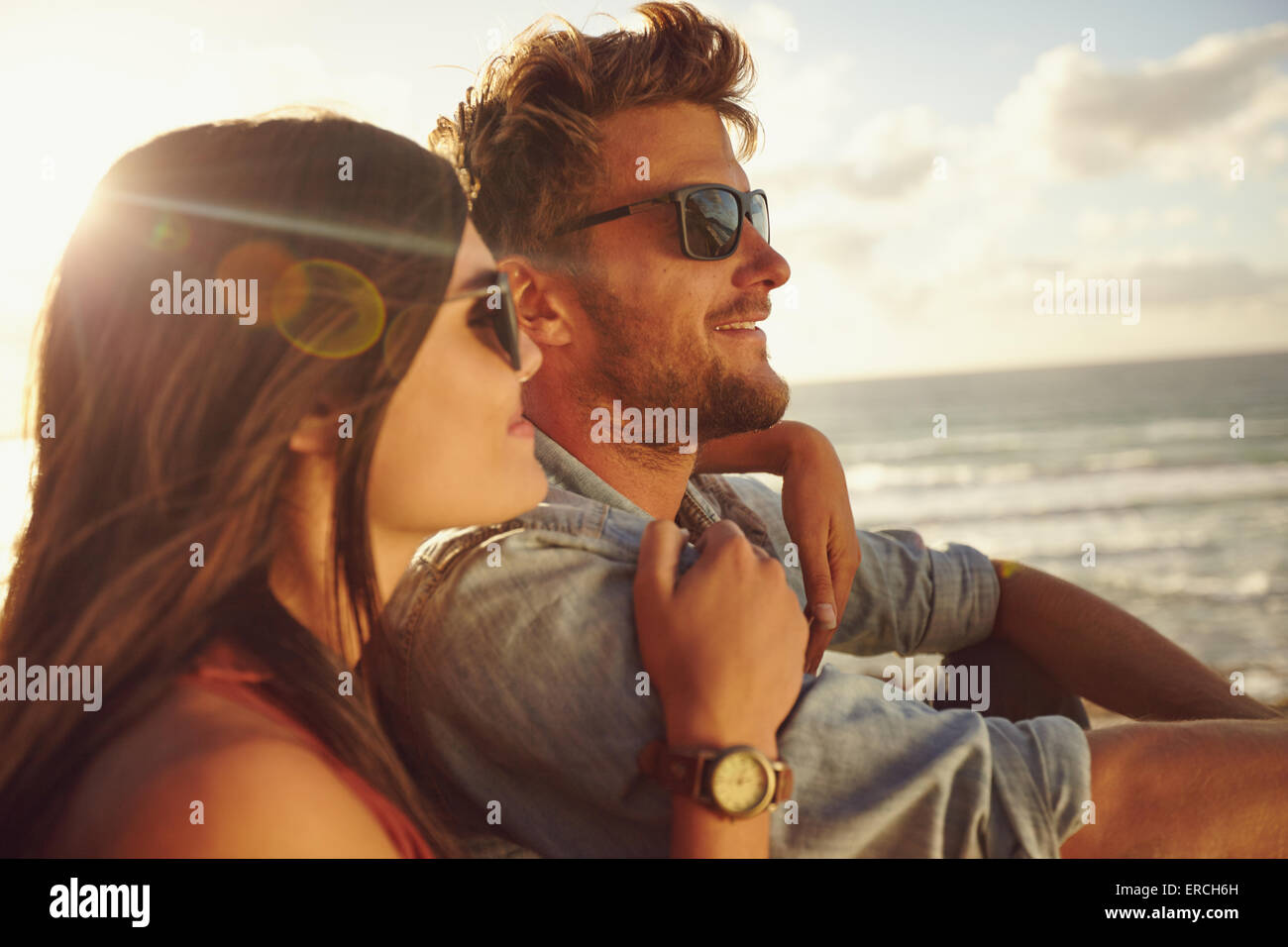 Romantic young couple together outdoors on a summer day. Caucasian couple enjoying the beach view. - Stock Image