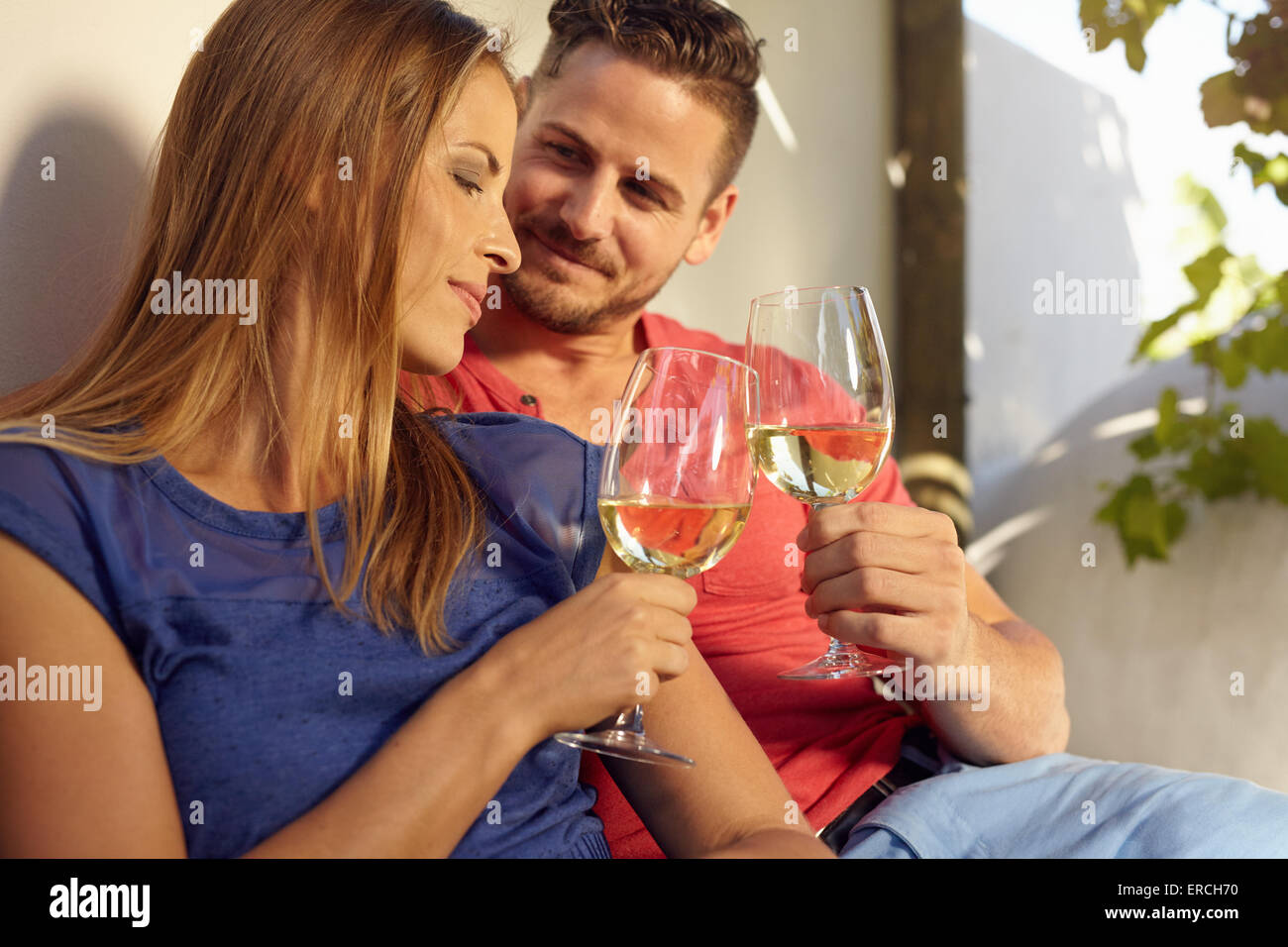 Young couple celebrating with white wine together, outdoors. Young man and woman toasting wine glass while sitting - Stock Image