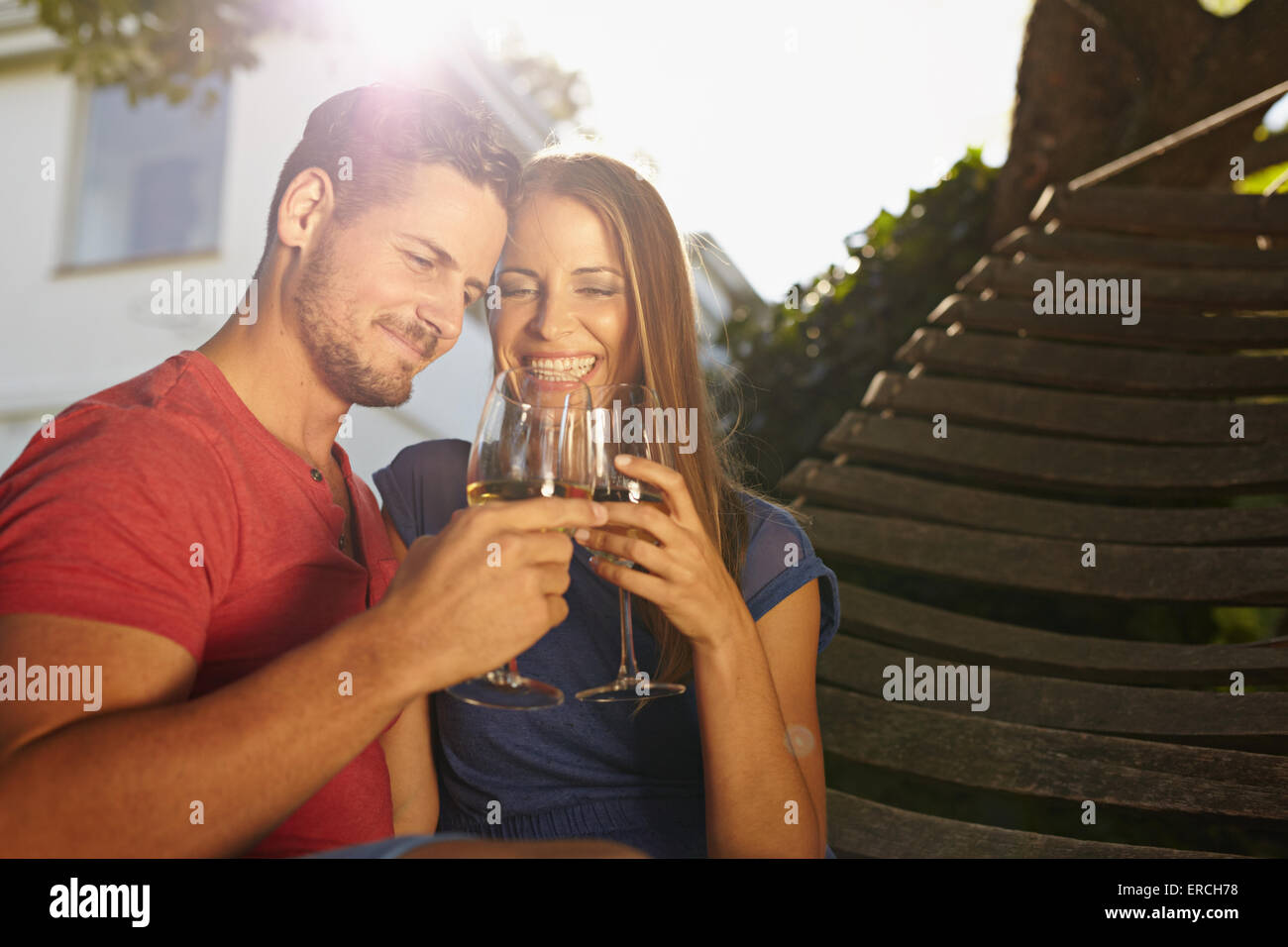 Outdoor shot of young caucasian couple in backyard toasting wine smiling. Romantic couple relaxing on hammock celebrating - Stock Image