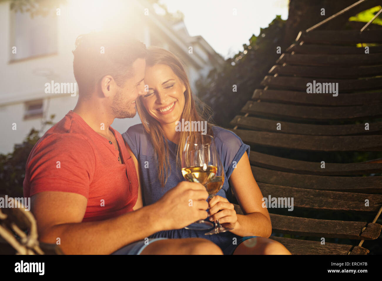 Beautiful young couple toasting wine outdoors. They are sitting on a hammock smiling and drinking wine with bright - Stock Image