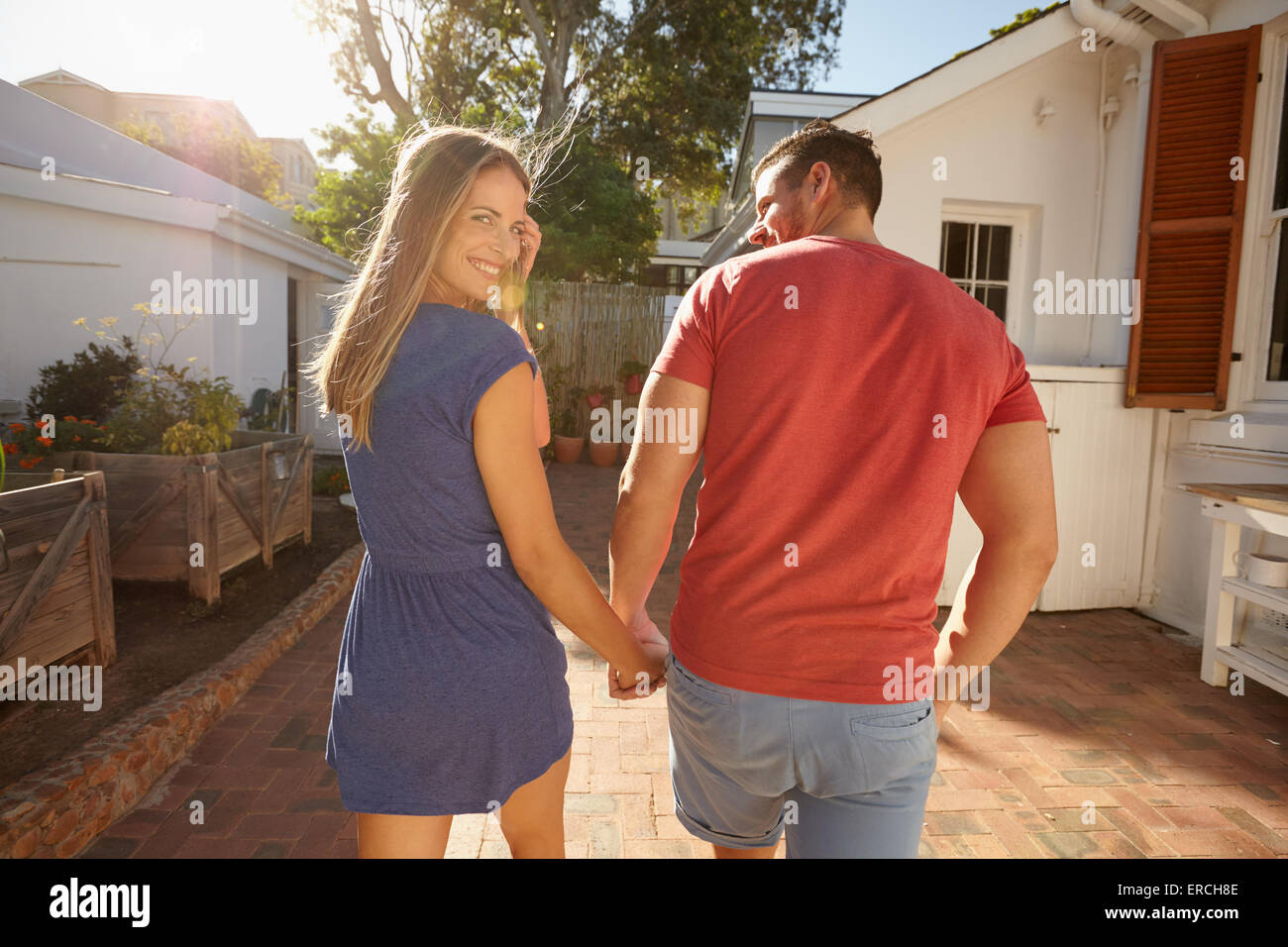 Young couple walking to their house holding hand in hand on a bright summer day, with woman looking back over shoulder and smili Stock Photo