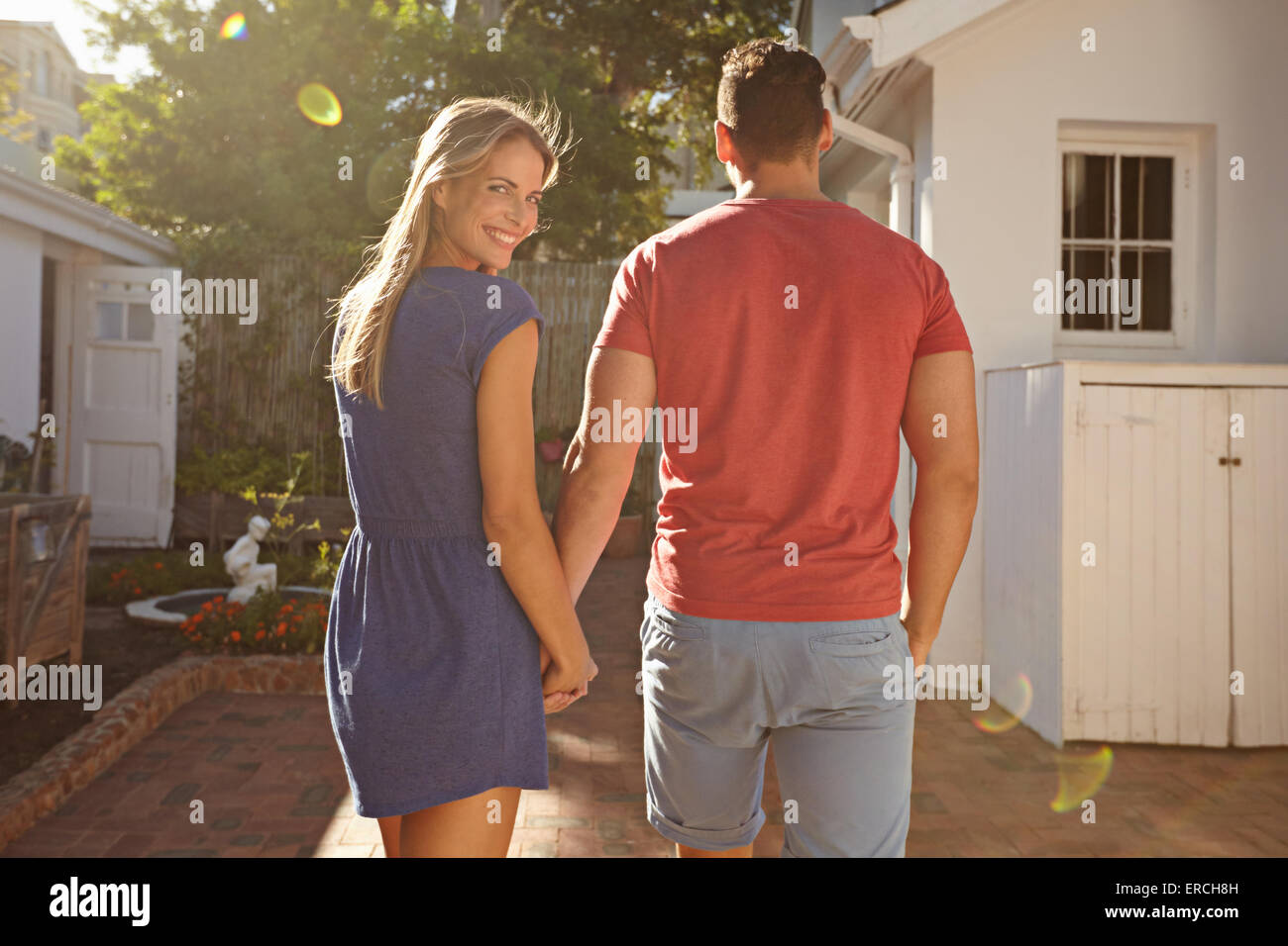 Young caucasian couple walking in the backyard holding hand in hand on a bright summer day, with woman looking back - Stock Image