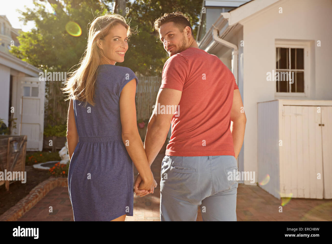 Shot of young couple in backyard on a bright sunny day. They are walking to their house hand in hand, looking over - Stock Image