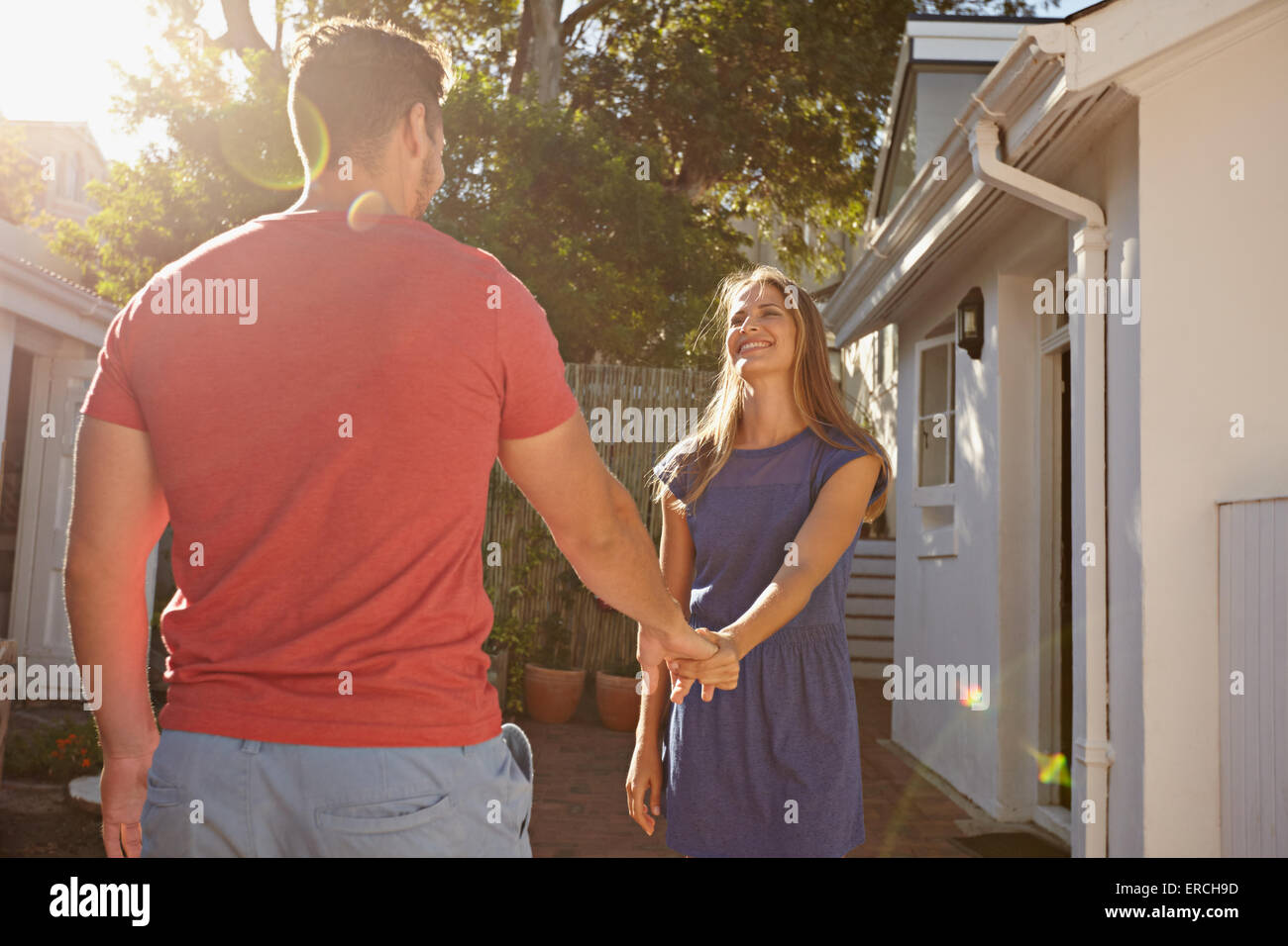 Happy young woman holding hand of her boyfriend and walking around their house. Loving young couple outdoors in - Stock Image
