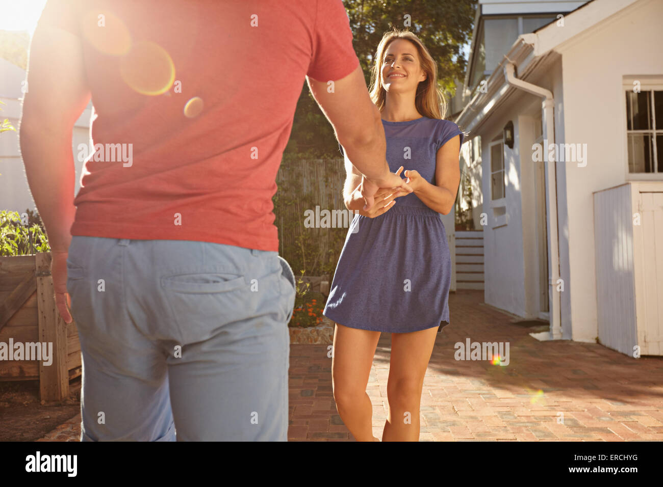 Couple outside their home with young woman pulling her boyfriend. Young woman holding hand of her boyfriend while - Stock Image