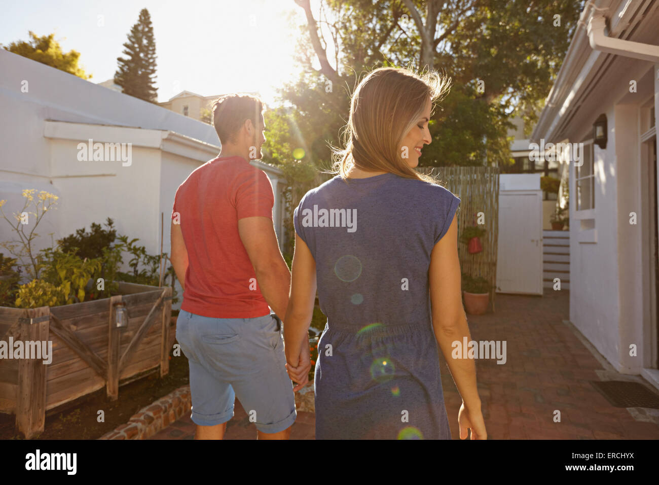 Rear view of young couple walking towards their house. Couple in backyard taking walk on a bright sunny day. - Stock Image